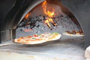 The Chefs carefully place the pizzas in the oven.