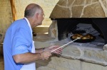 Rotating the chicken in our stone oven.